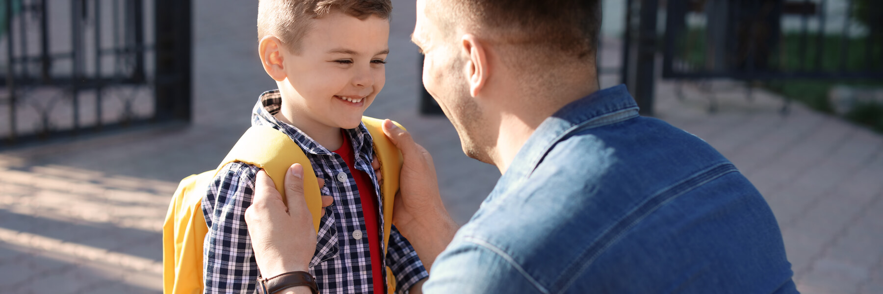 adult man helping young son or child put on school backpack properly, backpack safety concept