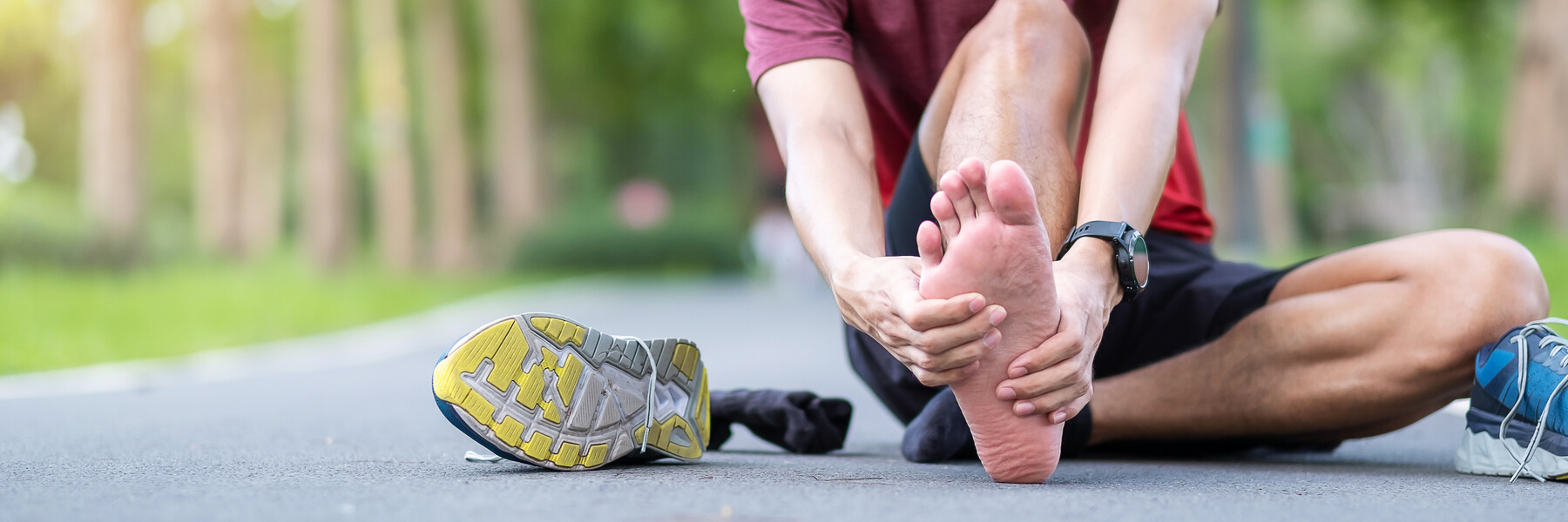Young adult male sitting on ground with his running shoe off, holding foot or heel muscle pain, runner having heel or foot ache or pain due to Plantar fasciitis